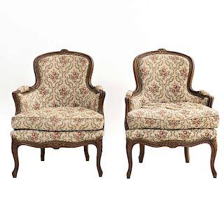 Par de sillones. Francia. SXX. Estilo Luis XV. En madera de nogal. Con respaldos cerrados y asientos con cojín en tapicería floral.