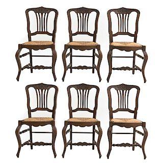 Lote de 6 sillas. Francia. Siglo XX. Estilo Luis XV. En talla de madera de roble. Con respaldos semiabiertos y asientos de palma.