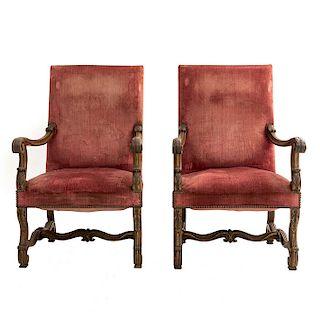 Par de sillones. Francia. Siglo XX. En talla de madera de nogal. Con respaldos cerrados y asientos acojinados en tapicería color rojo.