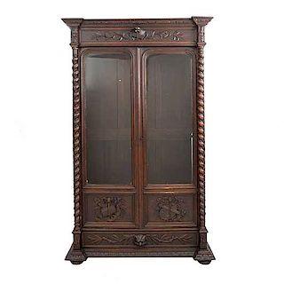 Librero. Francia. Siglo XX. En talla de madera de roble. Con cajón y 2 puertas abatibles con cristal. 167 x 145 x 47 cm.