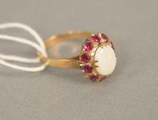 14K gold ring set with oval opal surrounded by red stones, size 7.