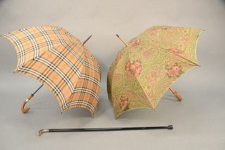 """Three piece lot to include a Burberry plaid umbrella with wood handle along with Lancel paisley umbrella, along with a walking stick. stick lg: 37"""" ."""