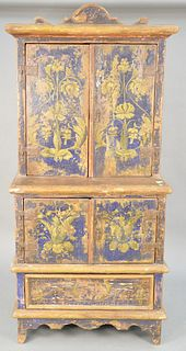 Primitive paint decorated cupboard, having two over two doors over one drawer, painted blue with yellow flower. ht. 74 in., wd. 35 in., dp. 24 in. Pro