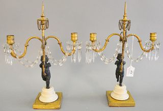 Pair of Louis XVI French candelabras, having cherub support, holding two gilt scrolling arms with crystal, bobeche and prisms, pricket central support