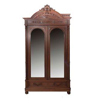 Armario. Francia. SXX. Estilo Enrique II. En talla de madera de nogal. 2 puertas abatibles, con espejo, cajón con tiradores de metal.
