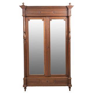 Armario. Francia. Siglo XX. Estilo Enrique II. En talla de madera de nogal. Con cajón y 2 puertas con espejos. 233 x 130 x 50 cm.