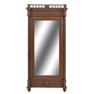 Armario. Francia. Siglo XX. En talla de madera de nogal. Con puerta con espejo de luna rectangular biselada. 235 x 109 x 60 cm.