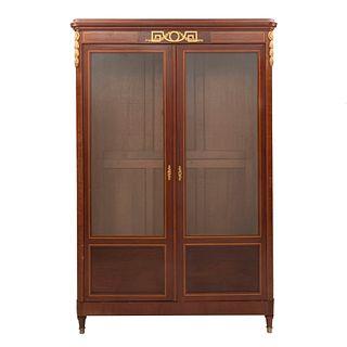 Librero. Francia. Siglo XX. Estilo Luis XVI. En talla de madera de nogal. Con 2 puertas abatibles con cristal. 204 x 136 x 43 cm.