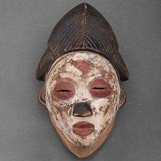 Máscara de Okuyi/Mukuyi. Gabón, Siglo XIX. Grupo étnico Punu. Talla en madera, pigmentos y caolín. Con escala en forma de diamante.