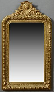 French Gilt and Gesso Overmantel Mirror, 19th c., with an arched shield and floral crest over a rounded corner frame with a large be...