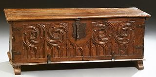 French Gothic Carved Walnut Coffer, 19th c., the lifting lid with iron strap hinges, corner braces and lock, over a front panel with...
