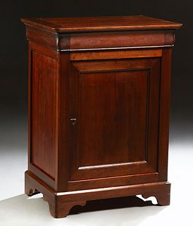 French Provincial Louse Philippe Carved Cherry Confiturier, 19th c., the rounded corner top over a frieze drawer and a cupboard door...