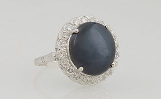 Lady's 14K White Gold Dinner Ring, with an 11.46 carat oval cabochon star sapphire, a top a border of round diamonds, total diamond...