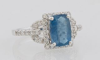 Lady's Platinum Dinner Ring, with an emerald cut 2.01 carat aquamarine, atop a rectangular border of round diamonds, flanked by pier...