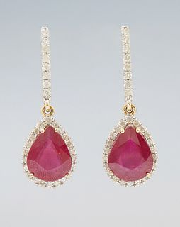 Pair of 14K Yellow Gold Pendant Earrings, each with a rigid diamond mounted link to a pear shaped pendant, with a pear shaped ruby a...