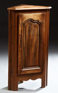 French Louis XIV Style Carved Oak Corner Cabinet, 20th c., the canted corner stepped edge top above an arched fielded panel door, on...