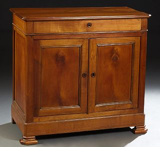 French Louis Philippe Carved Cherry Sideboard, late 19th c., the stepped canted corner top over a frieze drawer and double cupboard...