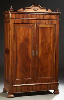 French Louis Philippe Carved Walnut Armoire, 19th c., the canted corner crown with an arched crest and turned finials, over double d...