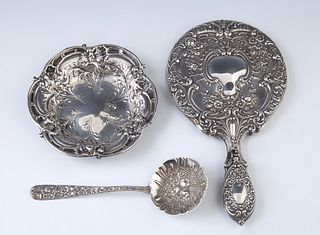 Three Pieces of Sterling, 20th c., consisting of an S. Kirk and Son repousse ladle with a floral relief handle; a Gorham Hand Mirror...