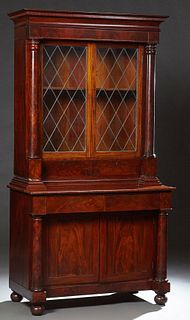 American Classical Mahogany Bookcase Cupboard, 20th c., the stepped ogee crown above leaded glazed double doors over two deep drawer...