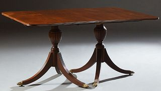 English Style Carved Mahogany Double Pedestal Dining Table, 20th c., the reeded edge rounded corner top on reeded urn supports to li...