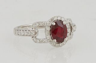 Lady's 14K White Gold Dinner Ring, with an oval 1.15 carat ruby a top a border of round diamonds, with pierced diamond mounted lugs,...
