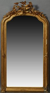 French Louis XVI Style Gilt and Gesso Overmantel Mirror, 19th c., the arched serpentine top with an elaborate bird, floral, torch an...