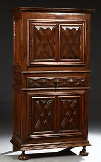 French Provincial Louis XIII Style Carved Walnut Homme Debout, 19th c., the stepped crown over a single cupboard door with iron fich...