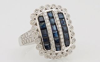 Lady's 14K White Gold Dinner Ring, the arched top with three parallel bands of princess cut blue sapphires, separated by diamond mou...