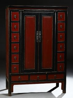 Carved Chinese Black and Red Lacquered Elm Apothecary Cabinet, 19th c., the rounded edge top over double doors flanked by six small...
