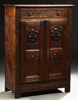 French Provincial Henri II Style Carved Oak Sideboard, 19th c., Brittany, the stepped rounded edge top over a long frieze drawer and...