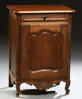 French Louis XV Style Carved Walnut Nightstand, c. 1860, the stepped rounded corner top above a frieze drawer and an arched fielded...