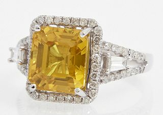 Lady's 14K White Gold Dinner Ring, with a 5.33 carat cushion cut yellow sapphire atop a border of pave diamonds, the pave diamond mo...