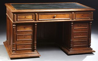 French Henri II Style Carved Walnut Desk, c. 1880, the stepped rectangular top with a leather insert writing surface over a center d...