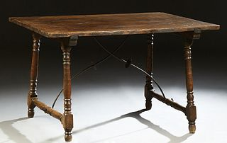 Spanish Provincial Carved Walnut Kitchen Table, 19th c., the rectangular top on turned and block trestle supports, joined by wrought...