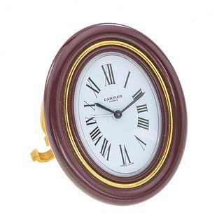 Reloj despertador Cartier Ref 7509. Movimiento manual. Caja oval en acero dorado. Bisel en resina color guinda.