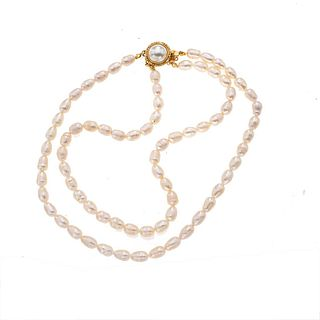 Gargantilla de perlas y metal base dorado. Diseño de dos hilos con 74 perlas cultivadas. Broche metal base dorado. Peso: 46.1 g.