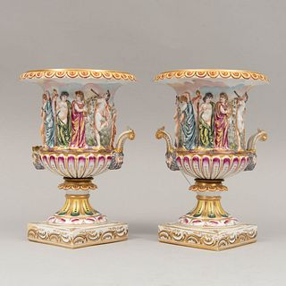 Par de copones. Italia. S XX. En porcelana Capodimonte. Con esmalte dorado, elementos orgánicos, florales, vegetales y escena griega.