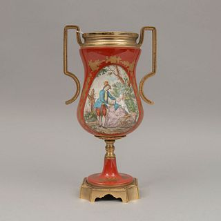 Tibor. Francia. Siglo XX. En porcelana y metal dorado. Decorado con escena bucólica y elementos florales. 33 x 18 x 13 cm.