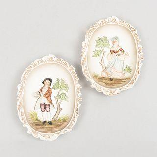 Par de medallones. Japón. Siglo XX. Elaborados en porcelana Lefton. Acabado gres. Decorados con pareja cortesana en bajo relieve.