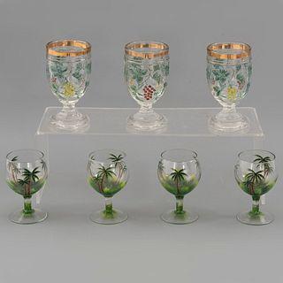 Lote de 7 copas. SXX. Elaboradas en cristal y vidrio prensado. Decoradas con elementos vegetales, frutales, palmeras y esmalte dorado.