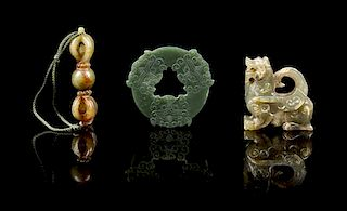 * A Group of Three Carved Jade Pendants Height of first 2 1/4 inches.