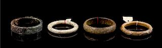 * A Group of Four Hardstone Bangles Diameter of largest 3 1/2 inches.