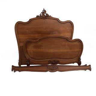 Cama matrimonial. Francia. Siglo XX. Estilo Luis XV. En talla de madera de nogal. Con cabecera, piecera y largueros.