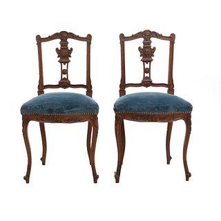Par de sillas. Francia. Siglo XX. Estilo Luis XV. En talla de madera de nogal. Con respaldos semiabiertos y asientos en tapicería azul.
