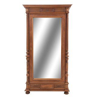 Armario. Francia. Siglo XX. Estilo Enrique II. En talla de madera nogal. Con puerta abatible con espejo. 216 x 117 x 54 cm.
