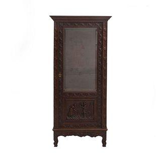 Vitrina. Francia. SXX. Estilo Bretón. En talla de madera de roble. Con puerta de cristal y soportes tipo roleo. 170 x 80 x 48 cm.