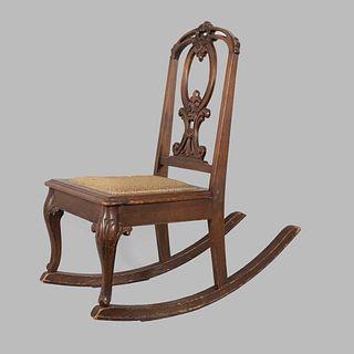 """Silla mecedora. Siglo XX. En talla de madera. Con respaldo semiabierto, asiento tejido, fustes semicurvos y soportes en """"ll""""."""