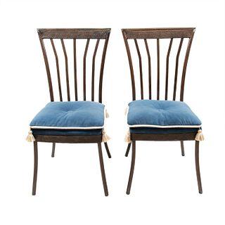 Par de sillas. Siglo XX. Elaboradas en metal. Con respaldos semiabiertos, asientos con cojines capitonados color azul.