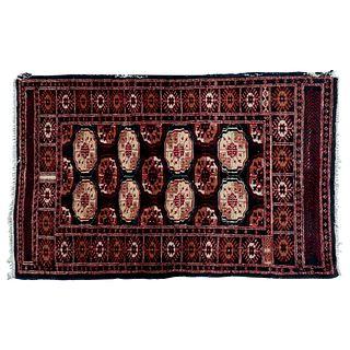 Tapete. Persia. Siglo XX. Estilo Bokhara. Elaborado en fibras de lana y algodón. Decorado con motivos geométricos. 147 x 96 cm